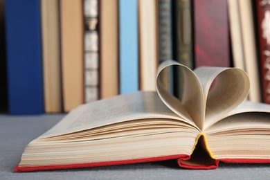 Open hardcover book on grey wooden table, closeup