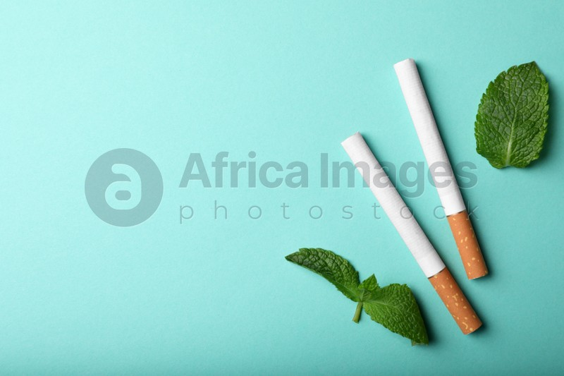 Menthol cigarettes and mint on turquoise background, flat lay. Space for text