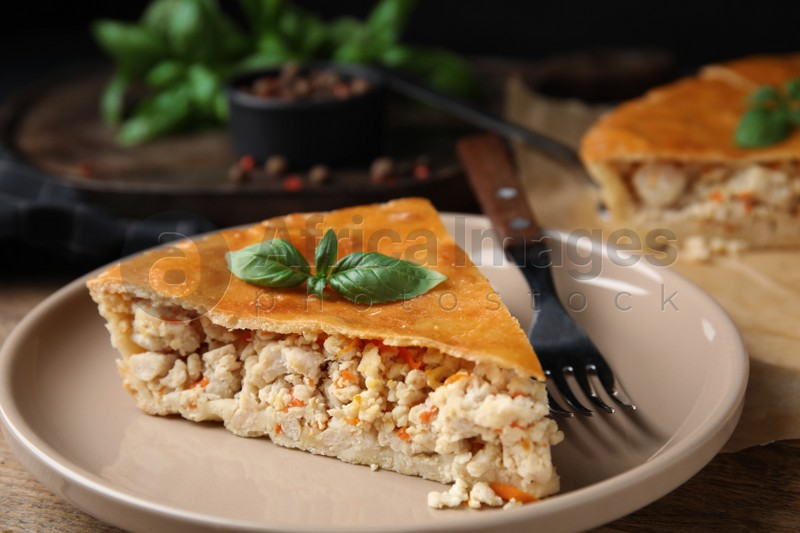 Piece of delicious pie with meat and basil on wooden table, closeup