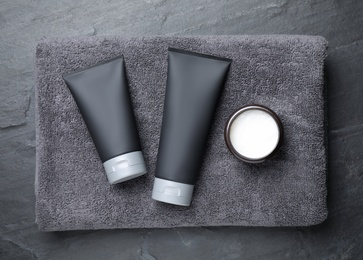 Set of men's cosmetic products with towel on grey stone table, top view