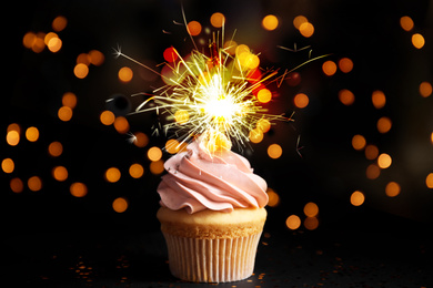 Delicious birthday cupcake with sparkler on black table against blurred lights
