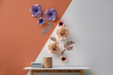 Books and holder on table near color wall with floral decor