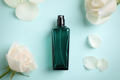 Bottle of perfume, beautiful roses and petals on light blue background, flat lay