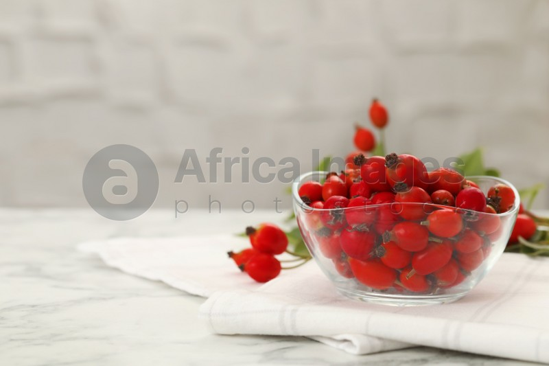 Ripe rose hip berries in bowl on white marble table. Space for text