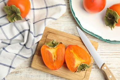 Tasty ripe persimmons on white wooden table, flat lay