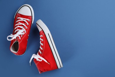 Pair of trendy sneakers on blue background, flat lay. Space for text