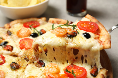 Taking slice of cheese pizza with seafood at table, closeup