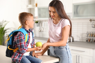 Happy mother giving apple to little child's with school bag in kitchen