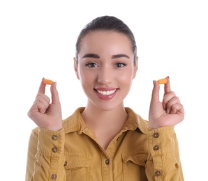Young woman with foam ear plugs on white background