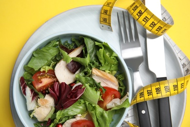 Plate of tasty salad, cutlery and measuring tape on yellow background, top view. Nutrition regime