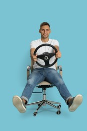 Happy man on chair with steering wheel against light blue background