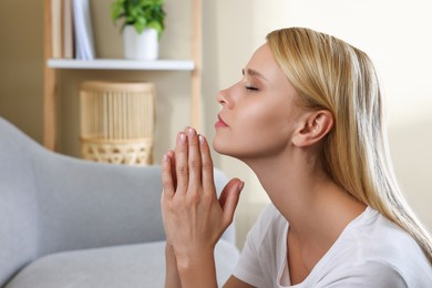 Religious young woman with clasped hands praying indoors. Space for text