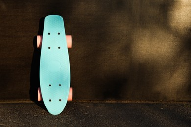 Modern light blue skateboard with pink wheels near black wall outdoors. Space for text