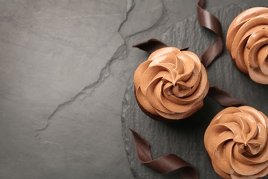 Delicious fresh chocolate cupcakes on black slate table, top view. Space for text