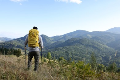 Tourist with backpack and trekking poles enjoying mountain landscape, back view. Space for text