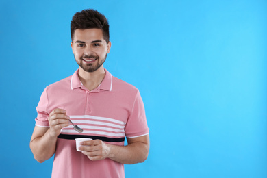 Happy young man with yogurt and spoon on light blue background. Space for text
