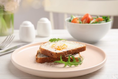 Delicious breakfast with fried egg, toasted bread and arugula served on white wooden table