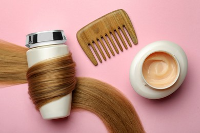 Bottle wrapped in lock of hair, jar and comb on pink background, flat lay. Natural cosmetic products