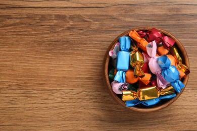 Bowl with candies in colorful wrappers on wooden table, top view. Space for text
