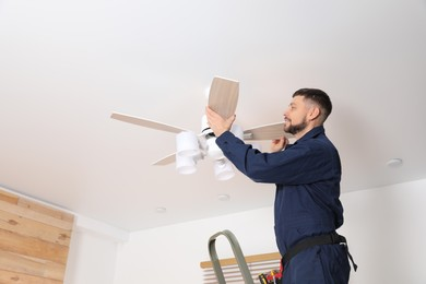Electrician repairing ceiling fan indoors. Space for text