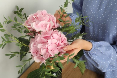 Woman with bouquet of beautiful hortensia flowers indoors, closeup
