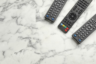 Modern tv remote controls on white marble table, flat lay. Space for text