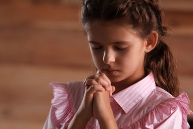 Cute little girl with hands clasped together praying on blurred background