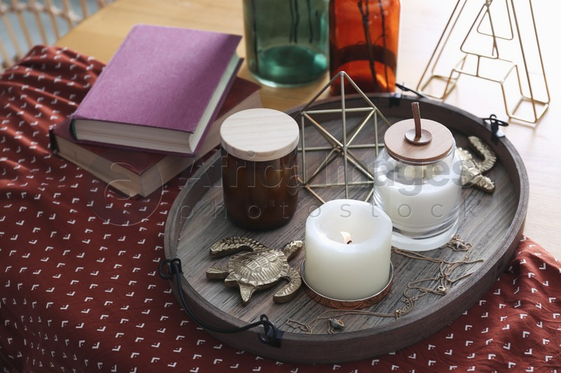 Wooden tray with decorations and books on table