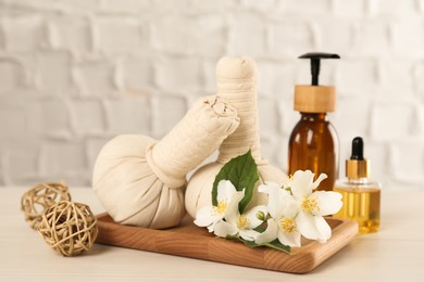 Beautiful jasmine flowers, herbal bags and skin care products on white wooden table