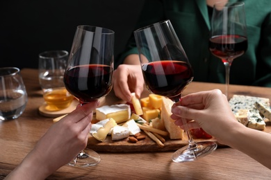 Women toasting with glasses of wine near cheese plate, closeup