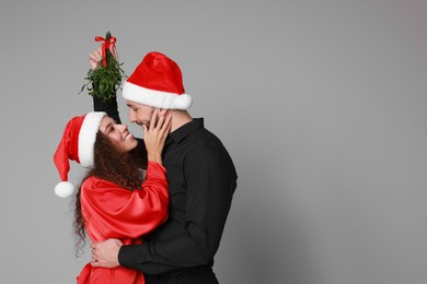 Lovely couple in Santa hats under mistletoe bunch on grey background. Space for text