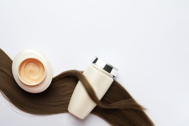 Natural cosmetic products and hair lock on white background, flat lay. Space for text