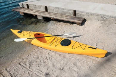 Yellow kayak with paddle on beach near river. Summer camp activity