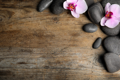 Stones with orchid flowers and space for text on wooden background, flat lay. Zen lifestyle