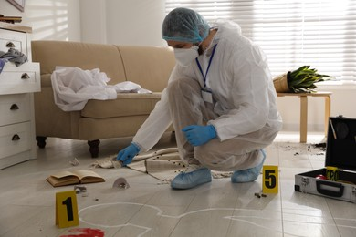 Investigator in protective suit working at crime scene
