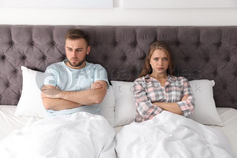 Young couple with relationship problems in bed at home