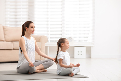 Young mother with little daughter practicing yoga at home