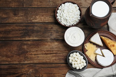 Flat lay composition with dairy products and clay dishware on wooden table. Space for text