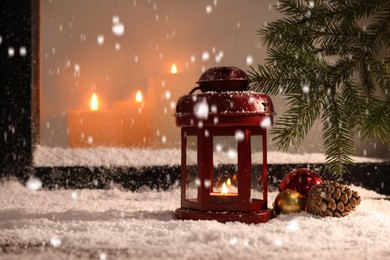 Snow falling onto window sill with Christmas lantern, outdoors. Space for text