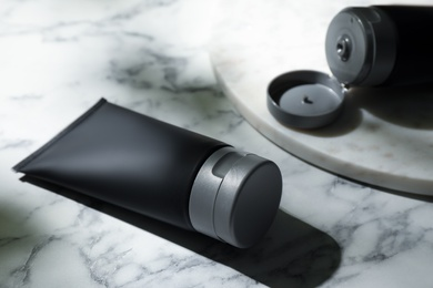 Men's cosmetic products in black tubes on white marble table, closeup