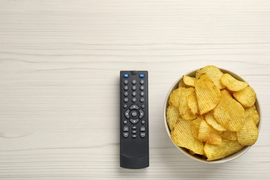Modern tv remote control and chips on white wooden table, flat lay. Space for text