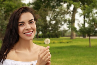 Beautiful young woman with dandelion in park, space for text. Allergy free concept