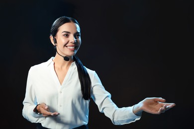 Motivational speaker with headset performing on stage. Space for text