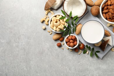 Vegan milk and different nuts on light table, flat lay. Space for text