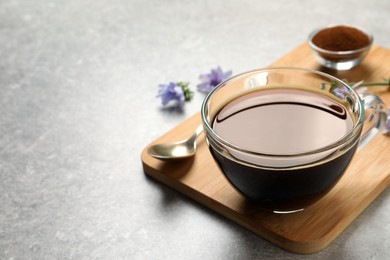 Glass cup of delicious chicory drink on light grey table, closeup. Space for text