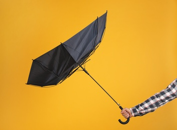 Man holding umbrella caught in gust of wind on yellow background, closeup