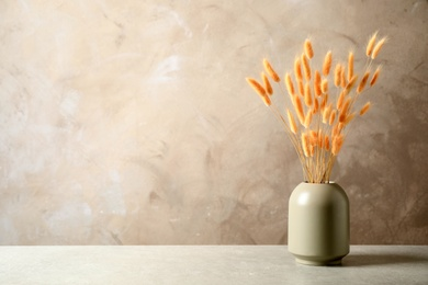 Dried flowers in vase on table against beige background. Space for text