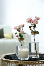 Burning candle and vases with beautiful roses on table indoors. Interior elements