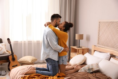 Lovely couple enjoying each other on bed at home