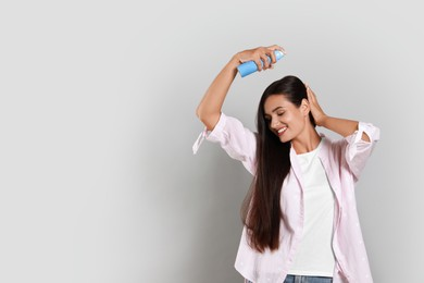 Woman applying dry shampoo onto her hair on light grey background. Space for text